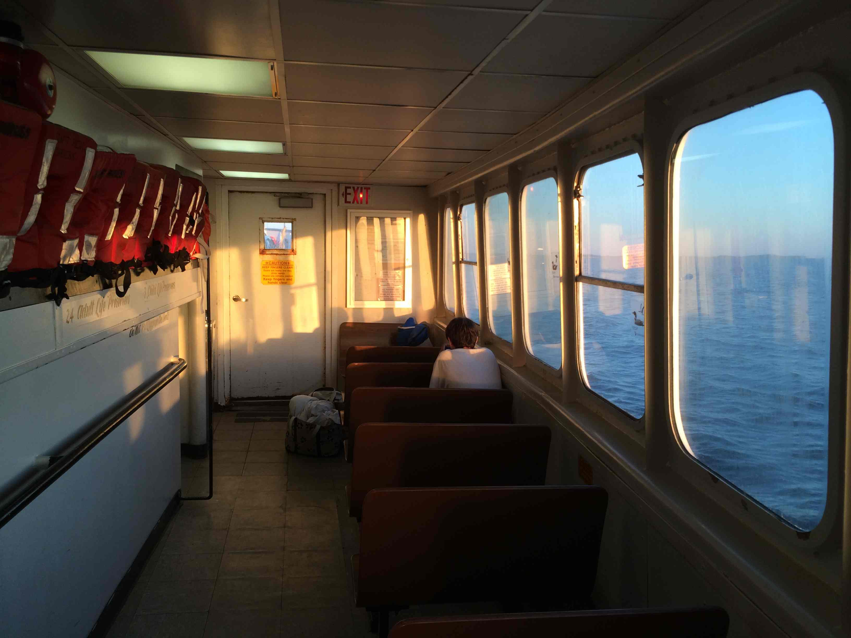 Jack on the almost empty ferry headed to North Haven. He was too busy reading to notice the light. Rhapsodies about the setting sun don't start happening until you are older anyway.