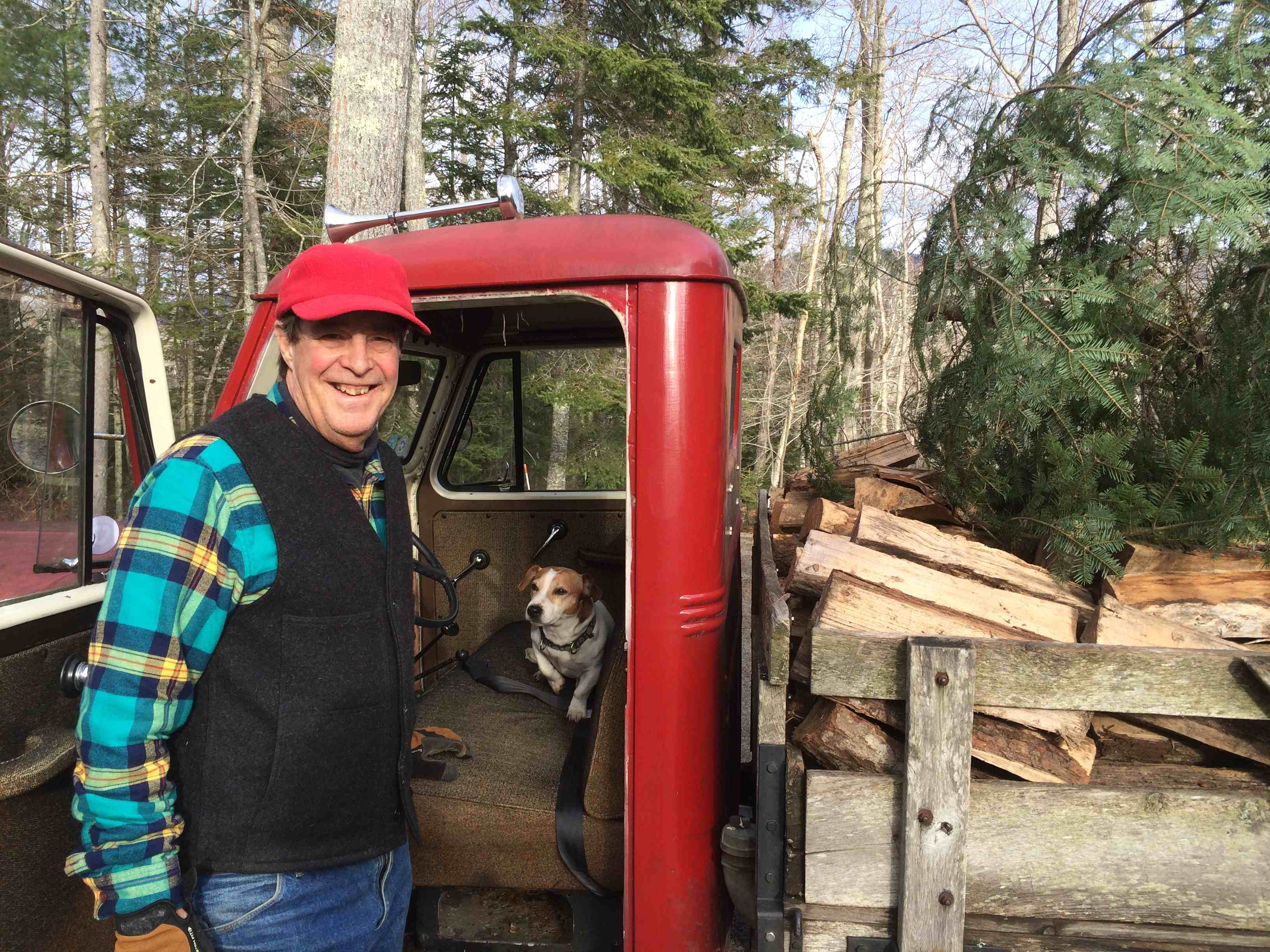 A proud tree hunter and his dog and his truck